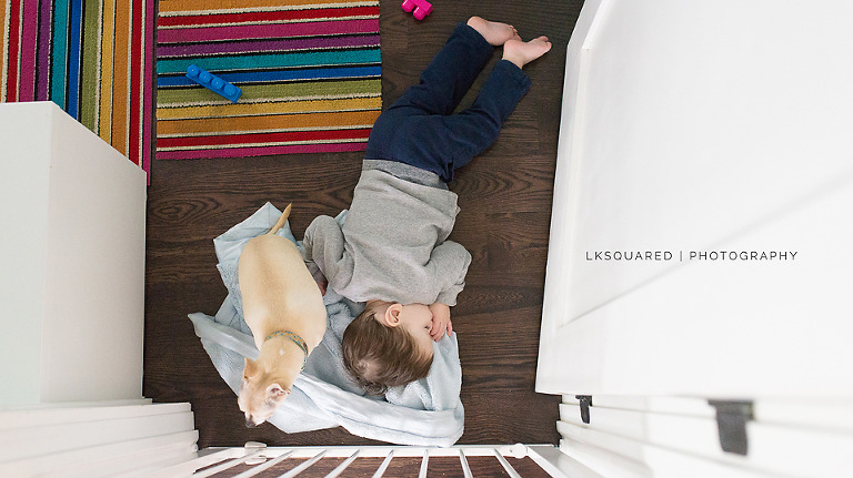 baby sleeping on the floor with his dog