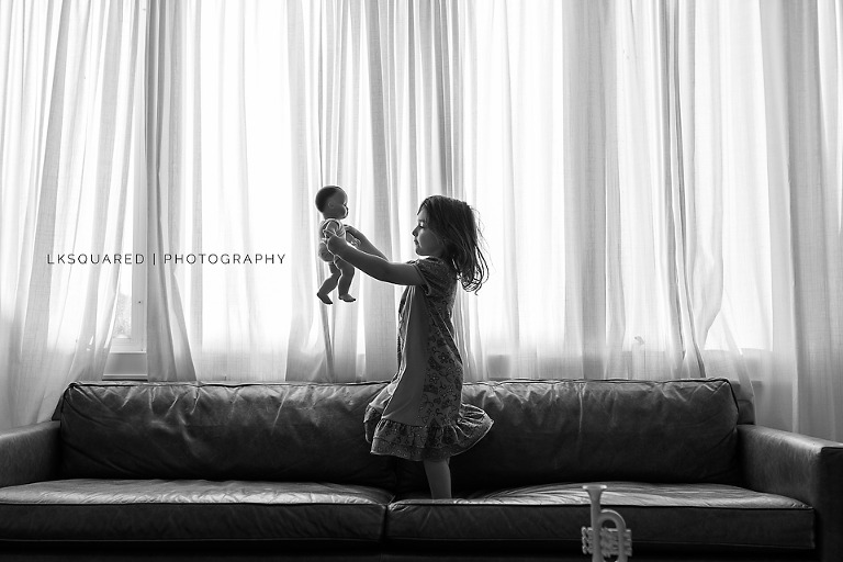 little girl dancing with her dolls on the couch in long beach long island