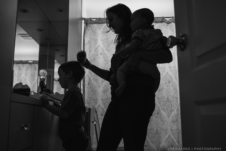 silhouette of mom brushing hair and carrying baby