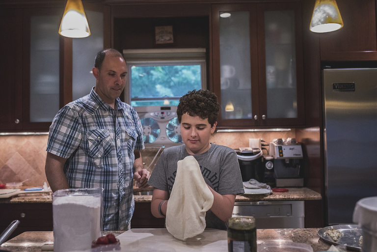 boy making pizza with dad