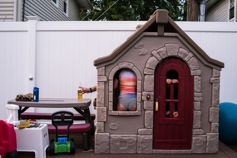 kids in playhouse while guy reaches for beer