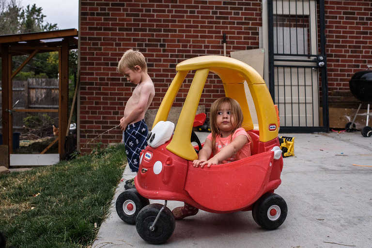 sister playing in play car while brother pees in yard