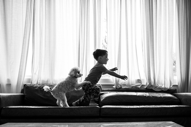 boy being chased by his dog for a hug