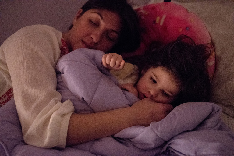 mom and daughter snuggling before bed