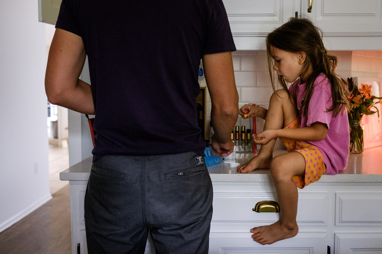 daughter on counter getting morning vitamins with dad